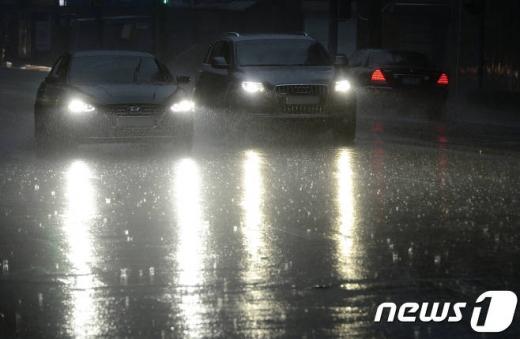 23일 오전 서울 종각역 인근에서 폭우가 내리자 차량들이 불을 켜고 운행하고 있다./사진=뉴스1DB