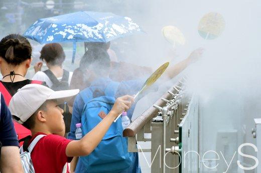 지난 21일 서울 종로구 광화문광장에서 시민들이 쿨 스팟(Cool Spot)을 지나며 더위를 식히고 있다. /사진=임한별 기자