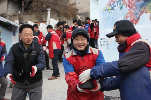 하석주(가운데) 대표이사가 롯데건설 샤롯데 봉사단과 함께 연탄을 나르고 있다. /사진=롯데건설