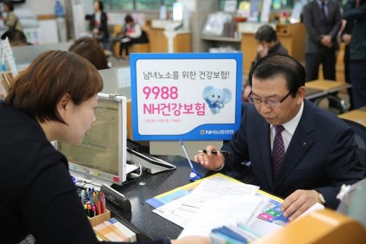 서기봉 NH농협생명 대표이사(오른쪽)가 '9988NH건강보험'에 가입하고 있다.