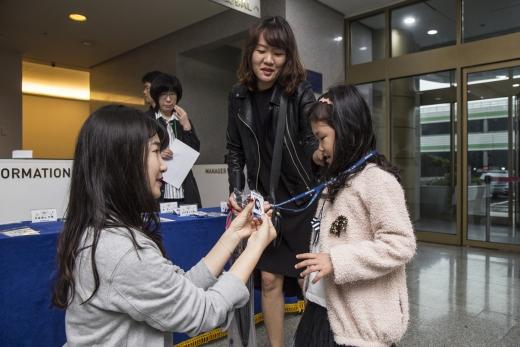 '해외근무 임직원 자녀 초청 행사'에서 현대엔지니어링 직원이 초청 자녀의 목에 이름과 사진이 새겨진 주니어 사원증을 걸어주는 모습. /사진=현대엔지니어링