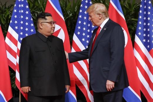 도널드 트럼프 미 대통령(오른쪽)이 12일 사상 첫 북미 정상회담이 열리는 싱가포르 카펠라 호텔에서 김정은 북한 국무위원장과 만나 서로 인사하고 있다. / 사진=AP·뉴시스
