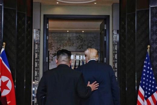 12일 김정은 북한 국무위원장과 도널드 트럼프 미국 대통령이 싱가포르 센토사섬 카펠라호텔에서 북미정상회담 합의문에 서명한 뒤 서명식장을 나서고 있다. /사진=싱가포르 통신정보부