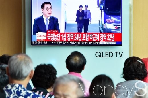 [머니S포토] '박근혜 징역 32년' 뉴스 보는 시민들