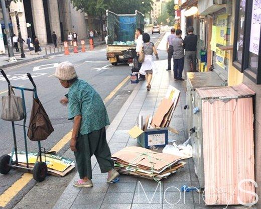 지난 18일 서울 광화문역 인근에서 한 노인이 폐지를 줍고 있다. /사진=강산 기자