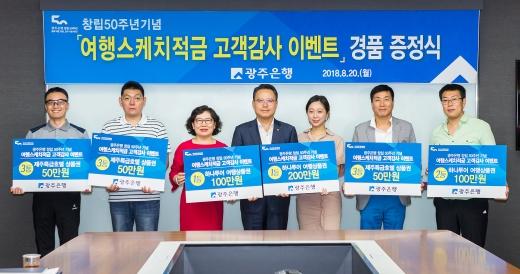 송종욱 광주은행장(가운데)이 '여행스케치적금 고객 감사' 이벤트 1~3등에 당첨된 고객들에게 경품을 전달하고 기념촬영을 하고 있다 .