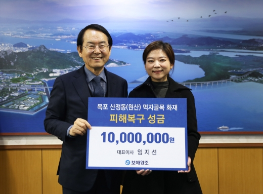 임지선 보해양조 대표(오른쪽)가 김종식 목포시장에게 신중앙시장 화재 피해복구 성금을 전달하고 있다.
