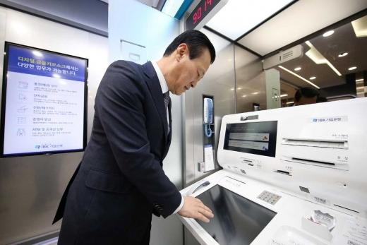 김도진 IBK기업은행장이 '디지털 뱅킹존'에 설치된 손바닥 정맥인증 솔루션을 시연하고 있다. / 사진=한국후지쯔.