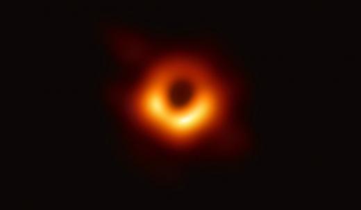 사상 최초로 공개된 초대질량 블랙홀 M87의 모습. 중심의 검은 부분은 블랙홀과 블랙홀을 포함하는 그림자이고, 고리의 빛나는 부분은 블랙홀의 중력에 의해 휘어진 빛이다. 관측자로 향하는 부분이 더 밝게 보인다. 블랙홀의 질량은 태양의 65억 배, 지름은 160억㎞에 달한다. /사진=EHT 홈페이지 캡처