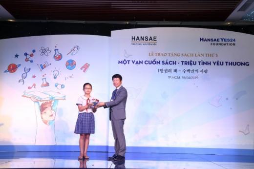 ©문양원 한세실업 베트남 총괄 법인장(오른쪽)과 책 기부를 받은 베트남 리엔민꽁놈 초등학교의 응웬우옌안트 학생(왼쪽)이 무대에서 기념 촬영을 하고 있다.