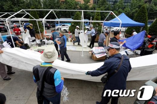 도널드 트럼프 미국 대통령의 방한을 하루 앞둔 28일 오전 우리공화당 당원들이 서울 광화문광장에 설치된 천막을 파이낸스센터 앞으로 옮기기 위해 철거하고 있다. /사진=뉴스1