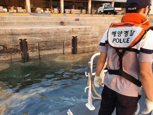 통영해양경찰서 경찰관이 지난 17일 오후 5시48분쯤 경남 남해군 남항 활어 위판장 앞바다에 유출된 경유를 방제하는 모습. /사진=통영해경