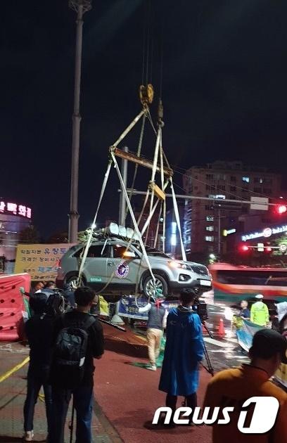 제주시 연동 신광사거리 앞에서 SUV차량에 타 크레인에 매달려 고공시위를 벌이던 노동자. /사진=뉴스1(제주소방안전본부 제공)