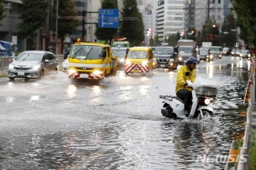 9일 제15호 태풍 '파사이'가 일본 도쿄에 상륙하면서  스쿠터를 탄 한 남성이 폭우로 침수된 도로를 건너고 있다./사진=뉴시스