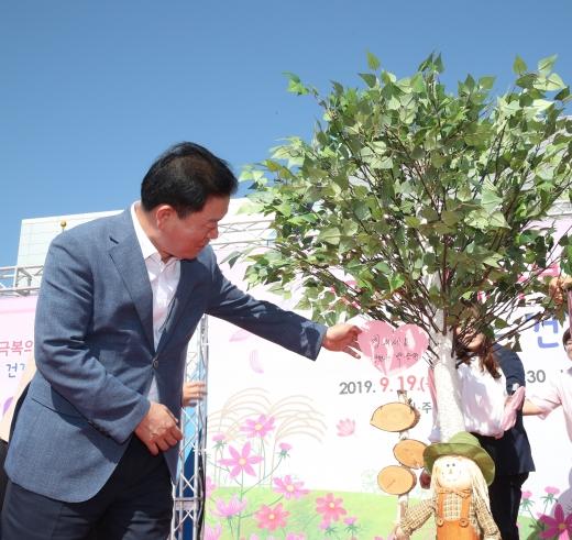 광명시는 9월19일 광명시민체육관에서 '2019 치매극복의 날 기념 행사'를 개최했다(박승원 광명시장이 '힘내세요' 희망메시지를 적어 나무에 매달았다). / 사진제공=광명시