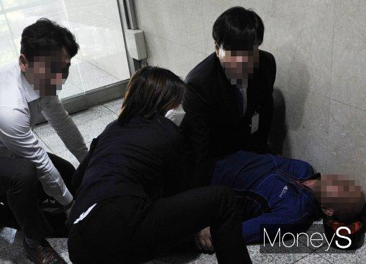 11일 오전 11시10분쯤 서울 여의도 국회 본관 기자출입문 인근에서 출입을 저지당한 60대 남성 A씨(오른쪽)가 농약성분의 물질을 마시고 쓰러지자 국회 직원들이 응급처치를 하고 있다. /사진=임한별 기자