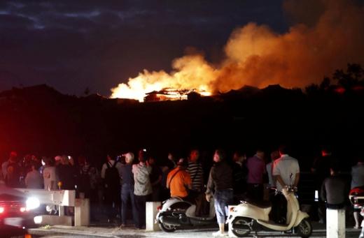 지난달 31일 일본 오키나와현 슈리성에서 발생한 화재를 인근 주민들이 나와 걱정스럽게 살펴보고 있다. /사진=로이터