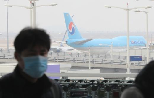 지난 2일 인천국제공항 계류장에 주기된 항공기 앞으로 마스크를 쓴 여행객이 지나가고 있다. /사진=뉴스1
