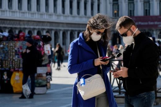 코로나19가 기승을 부리는 이탈리아에서 한 여행객들이 마스크를 쓴 채 사진을 보고 있다. /사진=로이터