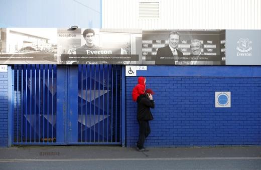 코로나19 여파로 잉글랜드 프리미어리그 일정이 다음달 초까지 취소된 가운데, 영국 리버풀 구디슨 파크 앞을 시민들이 지나고 있다. /사진=로이터