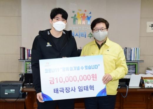 임태혁 씨름선수(왼쪽)가 염태영 수원시장(오른쪽)에게 기부금 1000만 원을 전달한 후 함께하고 있다. / 사진제공=수원시