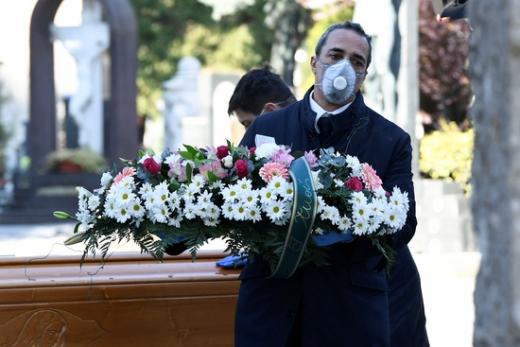 이탈리아에서 장례업체 직원들이 마스크를 쓴 채 장례를 집도하고 있다. /사진=로이터
