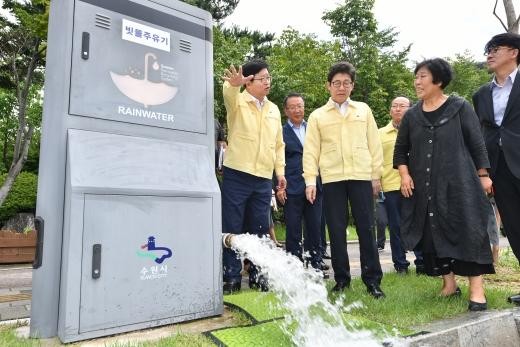 염태영 수원시장이 조명래 환경부장관에게 레인시티 사업 중 하나로 활용되는 빗물주유기를 설명하고 있다. / 사진제공=수원시