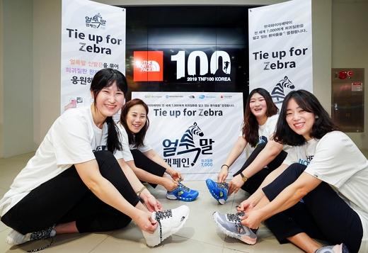 한국화이자제약 임직원이 노스페이스 명동점에서 '얼룩말 캠페인, TIE UP FOR ZEBRA' 론칭을 위한 기념 사진을 촬영하고 있다./사진=한국화이자제약