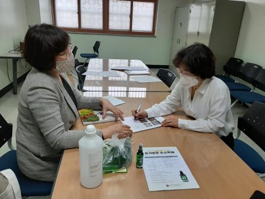 수원시자원봉사센터 소속 교육강사단 봉사자가 영덕중학교 교사에게 슬기로운 손소독제 만들기를 설명하고 있다. / 사진제공=수원시자원봉사센터
