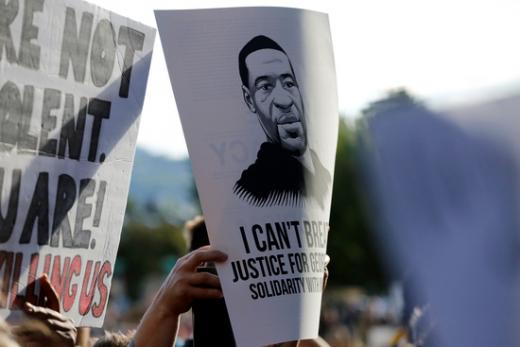미국 오리건주 포틀랜드에서 인종차별 반대 시위자가 조지 플로이드의 얼굴이 새겨진 플래카드를 들어보이고 있다. /사진=로이터