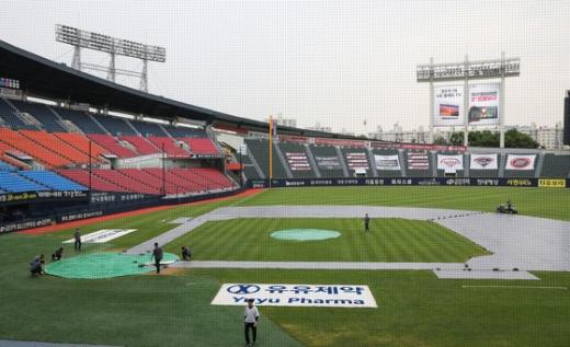 지난 10일 SK 와이번스와 LG 트윈스의 프로야구 경기가 예정된 서울 송파구 잠실야구장에 비가 내려 직원들이 방수포를 덮고 있다. /사진=뉴스1