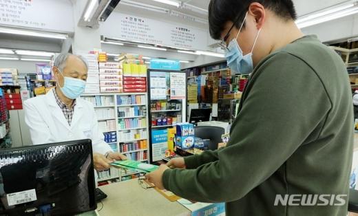 서울 종로의 한 약국에서 시민이 공적 마스크를 구매하고 있다./사진=뉴시스