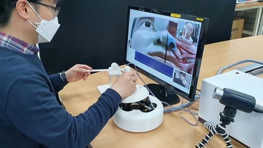 로봇 시스템은 의료진이 조작하는 '마스터 장치', 환자와 접촉하는 '슬레이브 로봇'으로 이뤄진다. 사진은 원격 검체 채취 로봇 작동 예시./사진=한국기계연구원