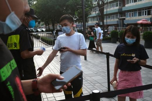 중국 베이징에서 한 시민이 마스크를 쓴 채 체온을 체크하고 있다. /사진=로이터