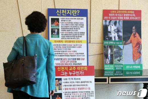 지난달 30일 서울 영등포구 여의도 CCMM빌딩에서 열린 신천지·동방번개 대책 기자회견에서 한 참석자가 신천지 관련 피켓을 보고 있다./사진=뉴스1DB