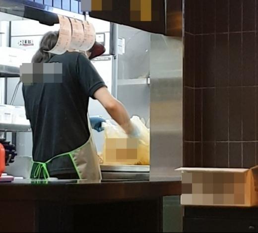 지난 10일 한 온라인 커뮤니티에 모 프랜차이즈 치킨 브랜드 매장에서 치킨 포장용 봉지에 시즈닝 가루를 버무리고 있는 사진이 게재돼 논란을 빚었다. /사진=온라인 커뮤니티 캡처