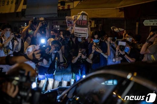 지미 라이가 탑승한 차를 둘러싼 취재진과 지지자들. © AFP=뉴스1