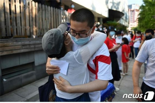 중국 수도 베이징시 당국이 방역지침을 대폭 완화했다. 사진은 베이징에서 코로나19로 한달 연기된 대학 입학시험인 '가오카오'를 치르는 마스크를 쓴 수험생이 시험장에 들어가기 전에 어머니와 포옹하고 있는 모습./사진=뉴스1