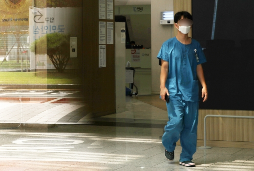 의과대학 정원 확대 등 정부 의료 정책에 반대하는 전공의들이 집단 휴진에 돌입한 21일 서울 종로구 서울대병원에서 의료진이 병원을 지나고 있다./사진=김휘선 머니투데이 기자