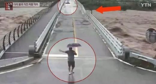 평창군이 지난 3일 공개한 인근 CCTV 영상에 따르면 평창군 진부면 주민은 송정교가 붕괴되기 직전 다리 건너편에 있는 차량이 다리로 진입하자 황급히 차량을 향해 뒤로 물러나라는 손짓을 보냈다. /사진=YTN 뉴스 화면 캡처