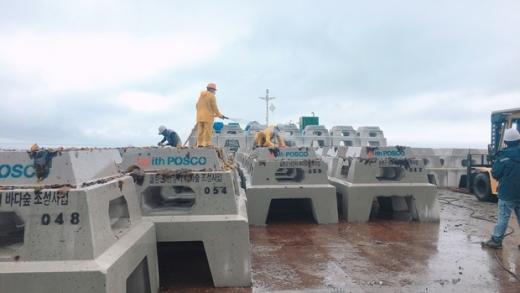 작업자가 트리톤에 어초를 이식하고 있다. /사진=포스코