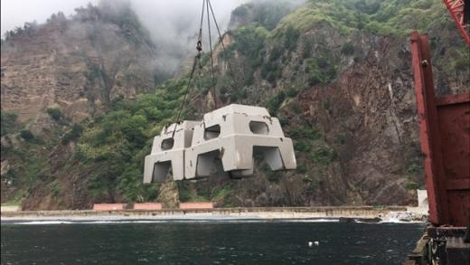 해저에 설치되기 위해 크레인으로 이송중인 트리톤. /사진=포스코