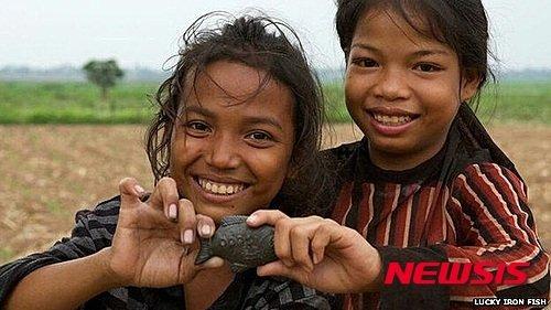 지난 2015년 캄보디아 소녀들이 철분 부족 해결을 위해 보급된 '철 물고기'를 들어 보이고 있다. /사진=BBC 캡처·뉴시스
