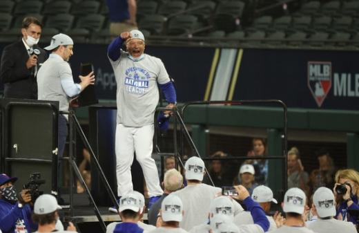 데이브 로버츠 LA 다저스 감독(단상 위)이 19일(한국시간) 미국 텍사스주 알링턴의 글로브 라이프 필드에서 열린 2020 메이저리그 NLCS 7차전 애틀란타 브레이브스와의 경기에서 4-3으로 승리한 뒤 진행된 축하 행사에서 선수들을 향해 주먹을 들어보이고 있다. /사진=로이터