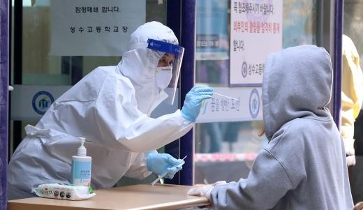 27일 서울 성수고 학생(오른쪽)이 교내에 마련된 선별진료소에서 코로나19 진단검사를 받고 있다. /사진=뉴시스