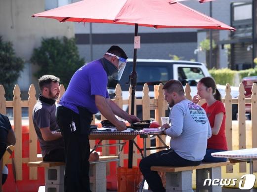미국 캘리포니아주 로스앤젤레스의 한 식당에서 직원이 음식을 서빙하고 있다. © AFP=뉴스1 자료사진