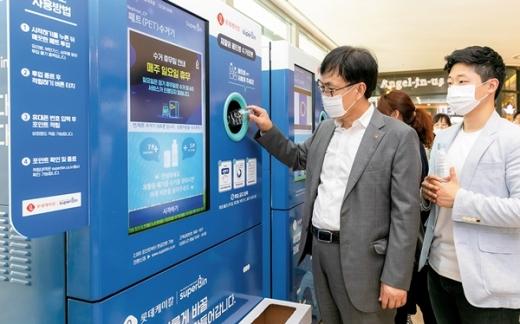 롯데그룹 김교현 화학BU장(왼쪽) 이 네프론 기계에 플라스틱페트병을 넣고 있다. /사진=롯데케미칼