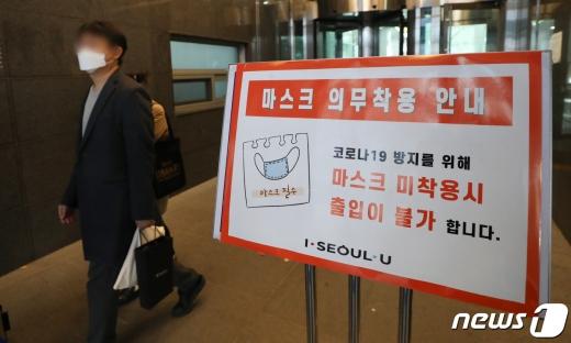 3일 서울시청 2층 기자실과 브리핑실에 폐쇄된 가운데 청사 출입구에 마스크 착용 안내 문구가 보이고 있다. /사진=뉴스1