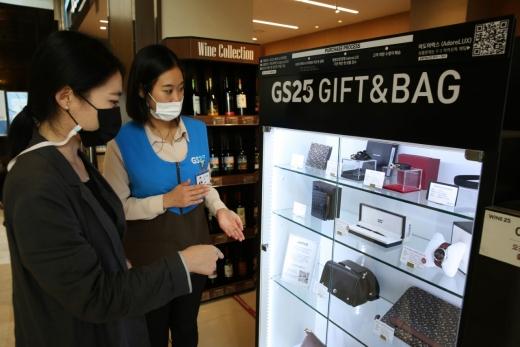 GS25 파르나스타워점 직원이 고객에게 명품 판매대에서 제품 설명을 진행하고 있다. /사진=GS25 제공