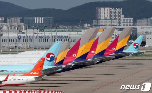 대한항공이 아시아나항공 인수를 검토하는 것으로 알려지면서 국내 1·2위 항공사의 합병에 관심이 쏠린다. 사진은 인천국제공항 주기장에 세워진 여객기의 모습. /사진=뉴스1